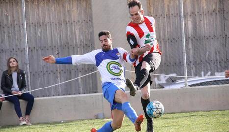 Un jugador del Bellcairenc colpeja la pilota tot i la pressió rival.