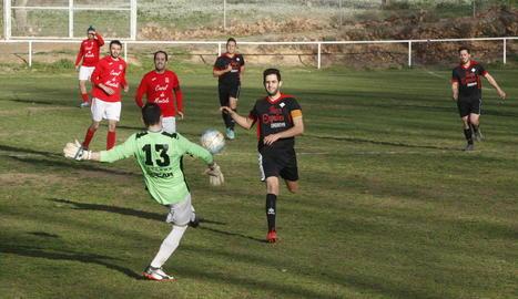 El porter del Montoliu allunya la pilota davant la pressió dels jugadors del Coll de Nargó.