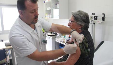 Un infermer administra la vacuna de a grip.