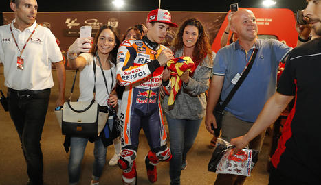 Marc Màrquez firma un autògraf a una aficionada, mentre altres es fan selfies amb el campió.