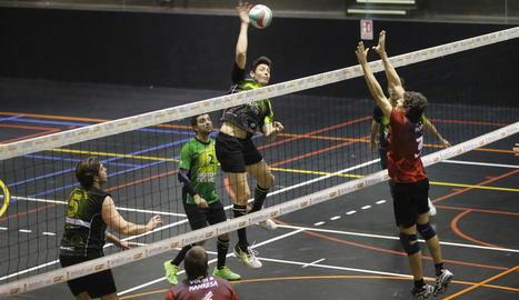 Un jugador del Balàfia intenta rematar una pilota davant el bloqueig d'un oponent del Manresa.