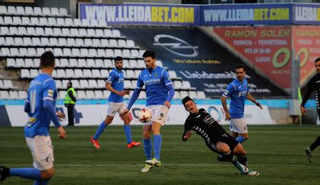 Eneko Satrústegui intenta controlar la pilota davant un jugador de l'Ebro que perd l'equilibri.