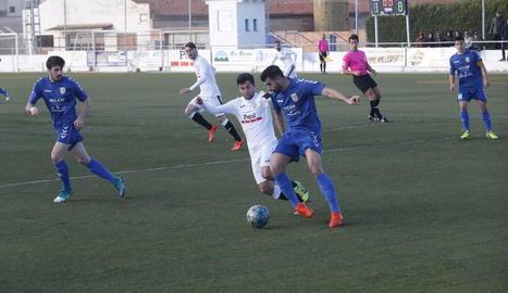 Un jugador del Borges persegueix la pilota davant la pressió de dos jugadors del Bellvitge.
