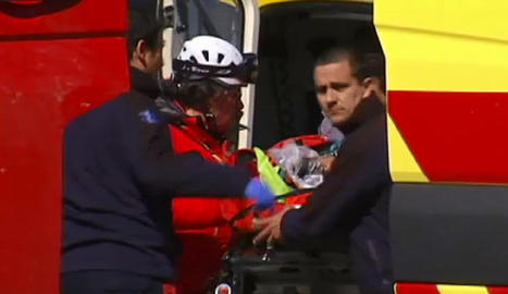 Un moment del rescat de les víctimes a la zona del sinistre. A la dreta, bombers amb el ferit.