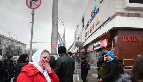 Una dona plora als voltants del centre comercial sinistrat.
