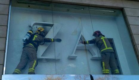 Els Bombers a l'aparador on hi va haver el foc.