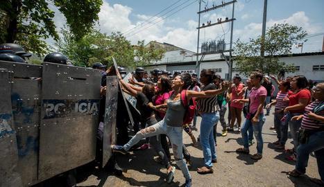 Un grup de familiars de presos protesta davant de membres de la policia.