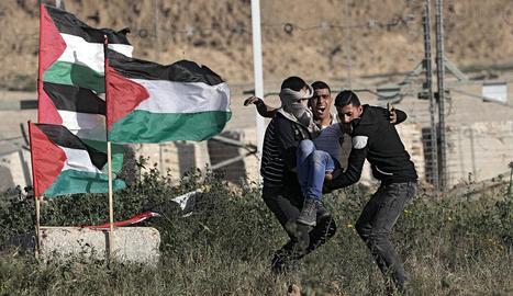 Diversos manifestants palestins retiren un jove que va resultar ferit a la frontera entre Israel i Gaza.