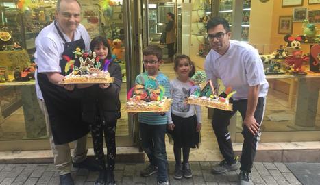 Els tres guanyadors posen amb les seues mones vora Pere Graells i el seu fill, Pere, davant de la pastisseria Graells de Balaguer, que regenten amb l'esposa de Pere, Judith Ávila