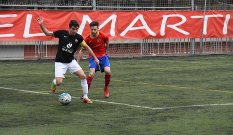 El capità de l'Alpicat controla la pilota davant la pressió d'un jugador del Martinenc.