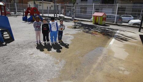 Un grup de nens de P-3 al pati de l'escola Joan Maragall, negat per l'aigua.