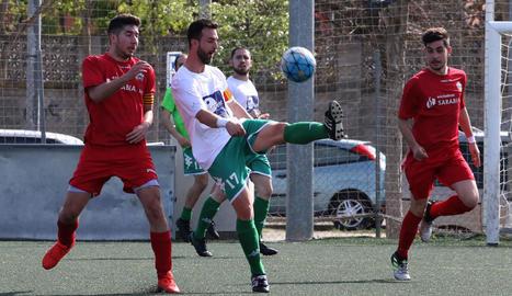 Un jugador del Balàfia controla la pilota davant de la presència de dos rivals.