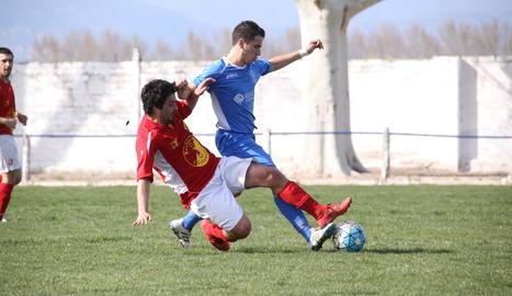 Un jugador de l'equip local i un del visitant es disputen per l'esfèric.
