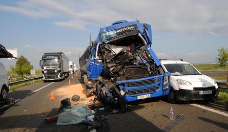 Imatge d'un dels camions implicats i al costat, la cua de vehicles.