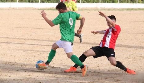Un jugador local intenta prendre la pilota a un de visitant.