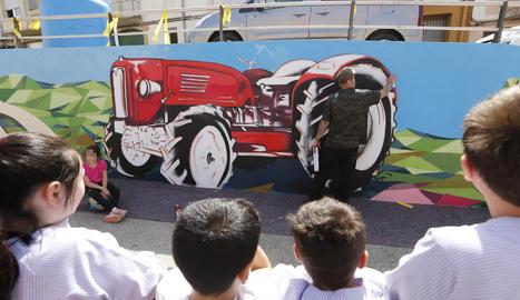 Diversos nens observaven ahir el grafiter Rulo mentre ultimava un mural a Corbins.