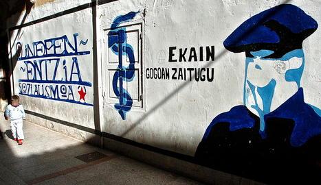 Un nen al costat d'un mural proetarra.