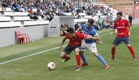 Javi López lluita una pilota davant d'un jugador de l'Olot.