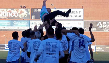 Els jugadors del Mollerussa i alguns aficionats celebren la victòria i l'ascens a Primera Catalana després de finalitzar el partit contra el Solsona.