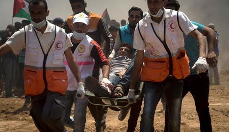 Efectius sanitaris evacuen un manifestant palestí ferit durant les protestes a la frontera.