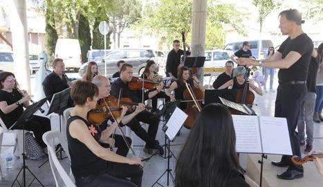 Diversos alumnes fan ballar una lona al ritme de les òperes que tocava l'orquestra.