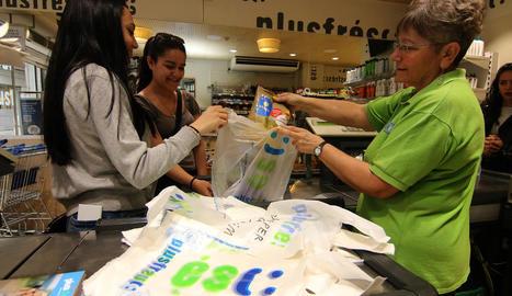 Una empleada d'un supermercat de l'Eix Comercial col·loca productes en una bossa de plàstic.