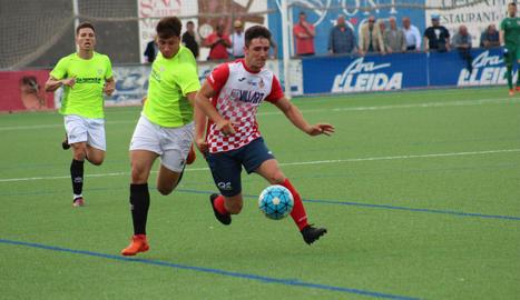Adrià, amb la pilota controlada, encara un jugador del Viladecans, amb dos rivals més a la vora i atents a la pilota.