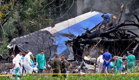 Policies i militars treballen entre les restes de l'avió.
