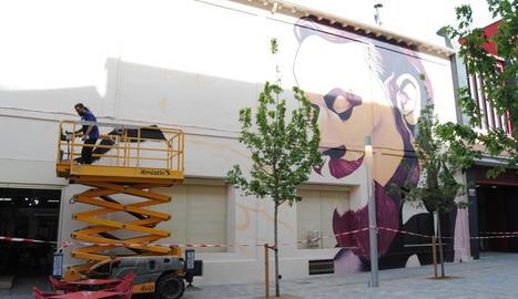 L'artista Sergi Gaya, ahir en plena acció pictòrica del mural en una façana de L'Amistat.