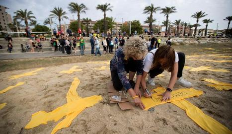 Dos joves col·loquen creus de tela grogues a la platja de Mataró, en una iniciativa del Comitè de Defensa de la República.