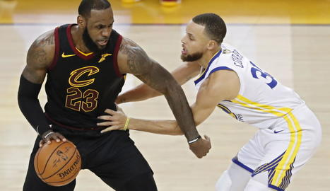 Stephen Curry defensa LeBron James, autor de 51 punts.
