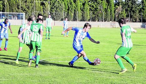 Un jugador del Torregrossa porta la pilota davant de la presència de diversos rivals, ahir durant el partit.