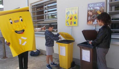 La mascota de la campanya, al costat dels punts de reciclatge.