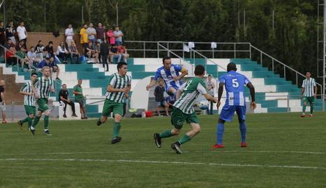 El capità del Torregrossa intenta passar la pilota a un company sota la pressió dels rivals.