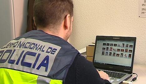 Un agent de la Policia Nacional revisa un ordinador requisat en l'operació.