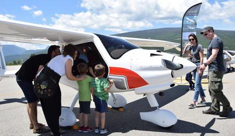 Visitants a l'aeroport de la Seu observen l'interior d'una avioneta ultralleugera.