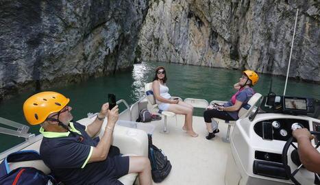 Turistes solcant el congost de Mont-rebei ahir a la tarda.  A la foto inferior a la dreta el vaixell passa per sota de la passarel·la per als vianants sobre el riu.