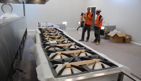 Treballadors en una de les cuines del nou obrador del grup Teresa Carles a Bell-lloc i, a la imatge dreta, Barri a la porta de la planta.