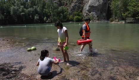 Un grup practica esports aquàtics a Gimenells i, a la imatge dreta, la vigilant de la zona de bany de Camarasa, que va començar a treballar ahir.