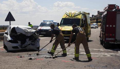 Dos bombers, treballant al lloc de l'accident al costat del cotxe en el qual viatjava la víctima mortal.