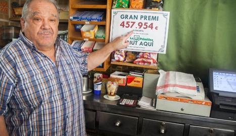 Jesús Morros, propietari del bar on es va segellar el bitllet guanyador, mostra el cartell del premi.