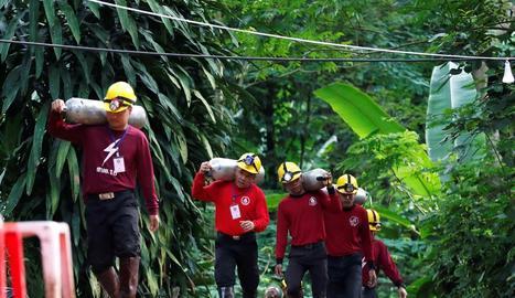 Els equips de rescat carreguen botelles d'oxigen.