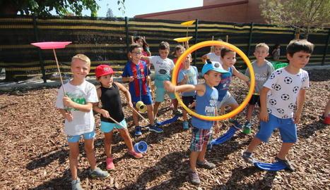 Un grup de nens amb diversos objectes per practicar jocs tradicionals ahir a Balàfia.