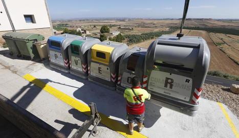 Operaris instal·lant els contenidors de recollida selectiva al costat dels vells en una de les illes delimitades per l'ajuntament d'Alfés.