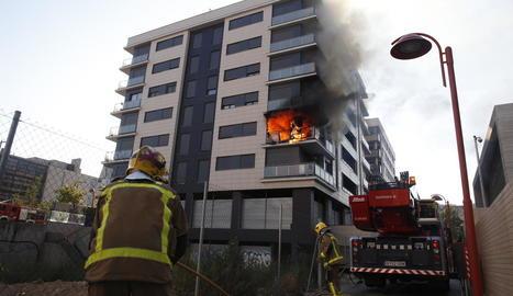 Els Bombers, segons abans de desplegar l'autoescala per apagar el foc, que es va originar en un balcó de la segona planta.