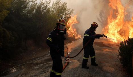 Diversos bombers proven d'extingir un incendi a Penteli, al nord de la capital de Grècia.