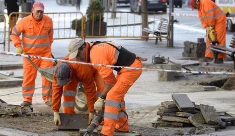 Operaris treballant en unes obres a la via pública.