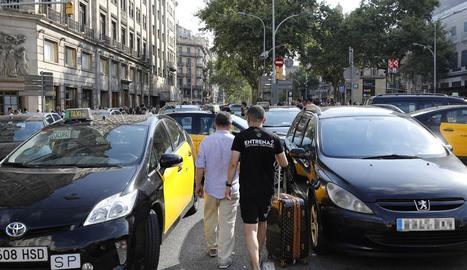 Diversos turistes passen entre els taxis que ocupen la Gran Via de Barcelona.