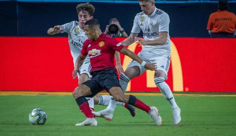 L'exblaugrana Alexis controla la pilota davant de dos madridistes.