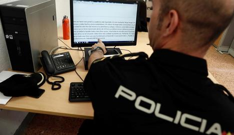 Un agent de la Policia Nacional mostra el correu electrònic que reben les víctimes de l'estafa.
